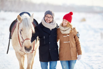 Couple Walking Horse Around Kentucky Horse Farm in Winter